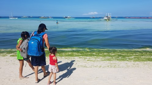A mother take hold on her two children as they ready to leave Boracay Island, not knowing the fate that awaits them somewhere.